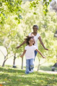 Grandmother and granddaughter running in the park