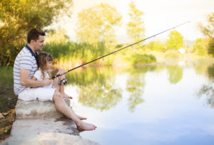 young father fishing on lake with his daughter