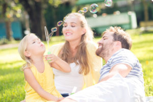 Couple and daughter blowing bubbles